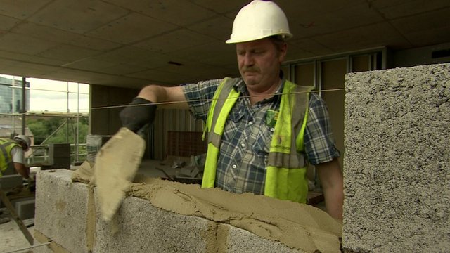 A builder laying blocks