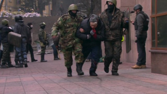 An injured protester is taken away in Kiev
