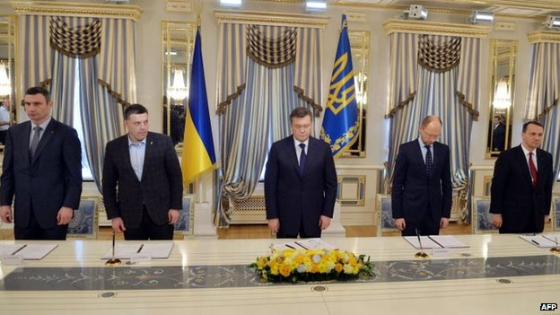 Ukrainian President Yanukovych (centre), opposition leaders and Polish Foreign Minister Radoslaw Sikorski sign the agreement