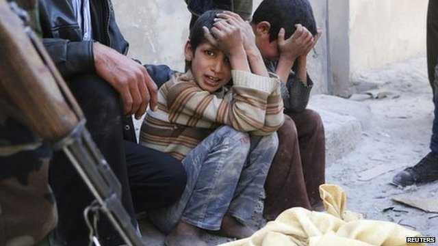 Children react next a body bag after what activists said was a barrel bomb attack in the al-Andhirat neighbourhood of Aleppo on 22 February.