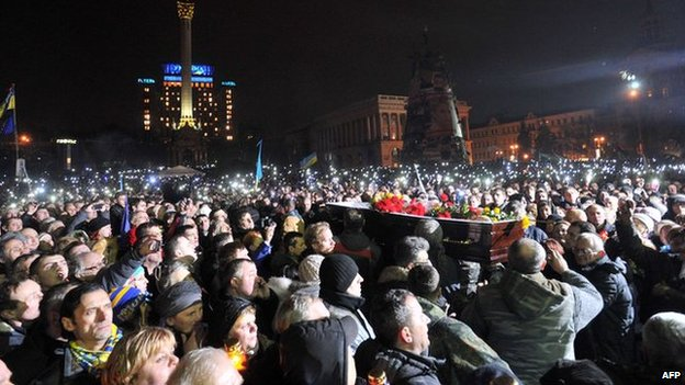 Crowds of protesters in Kiev with coffin of an activist killed in clashes