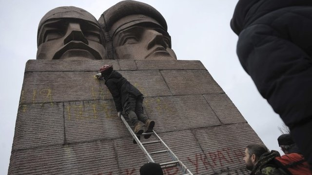 People paint on the KGB officers monument in Kiev, Ukraine