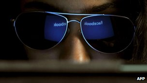 The Facebook logo is reflected in a young Indian woman's sunglasses