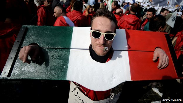 A protestor with his head and hands trapped in stocks in the colours of the Italian flag in a demonstration in Rome, 18 Feb 2014