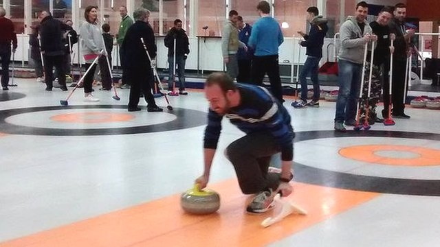People taking curling lesson