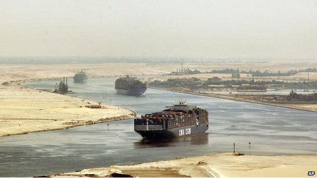 "FILE - In this Sept. 21, 2009 file photo, cargo ships sail through the Suez Canal, seen from a helicopter, near Ismailia, Egypt. Suez Canal authority chairman Mohab Mamish said Saturday, Aug. 31, 2013, that a ""terrorist element"" had tried to disrupt navigation in the waterway by targeting a Panama-flagged ship."