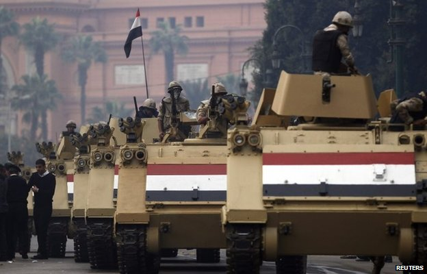 Soldiers in armoured personnel carriers arrive in Tahrir Square after clashes with pro-Morsi protesters in Cairo (1 December 2013)