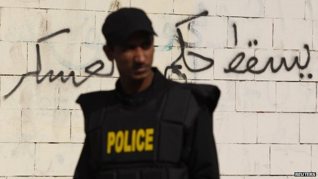 "A riot police officer stands guard at the scene of a bomb blast along a wall covered with graffiti around the Al-Azhar University campus in Cairo""s Nasr City district December 26, 2013. The bomb blast hit the bus on Thursday, injuring four people, a spokesman for Egypt's interior ministry told Reuters, two days after a car bomb killed 16 in the Nile Delta. That graffiti says, ""Down with military rule."""