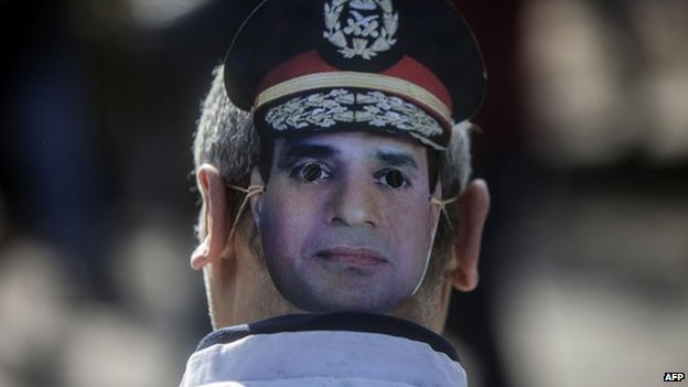 A supporter of Egypt's army chief Field Marshal Abdel Fattah al-Sisi, who is to run for the presidency in the upcoming elections, wears a mask bearing the image of the military commander