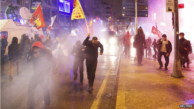 Protesters run away from water cannon and tear gas used by riot police during a demonstration against Turkey' Prime Minister Tayyip Erdogan in Istanbul on 25 February 2014.