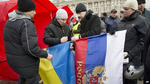 Pro-Russian activists tie together the Russian and Ukrainian flags as they gather below the statue of Vladimir Ilyich Lenin, in Donetsk,