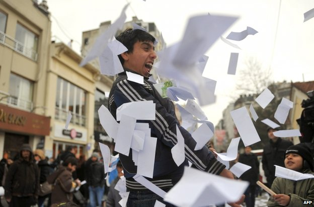 A man plays with fake euro banknotes at an anti-corruption rally in Istanbul, 26 February