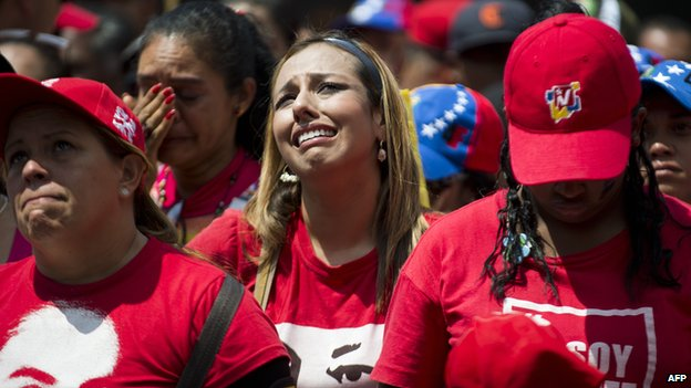 People cry as the coffin of Venezuelan President Hugo Chavez passes by them in Caracas on 15 March 2013