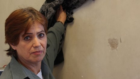 Fareeda, a prison guard shows the spot where a glass thrown at her hit the wall