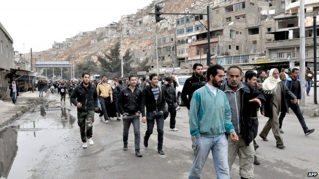 People return to their houses in the Barzeh district of Damascus (25 February 2014)