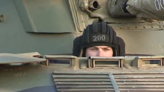 Russian soldier peering out of tank