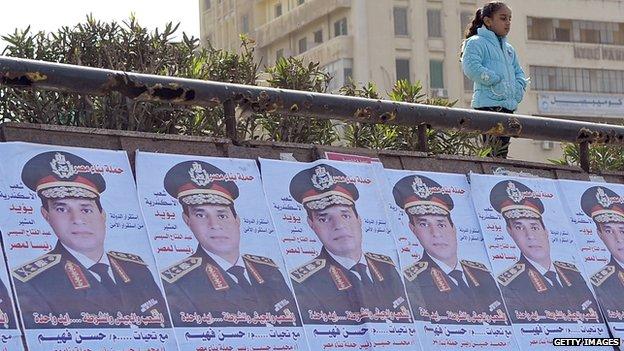 A girl stands above posters praising Abdel Fattah al-Sisi