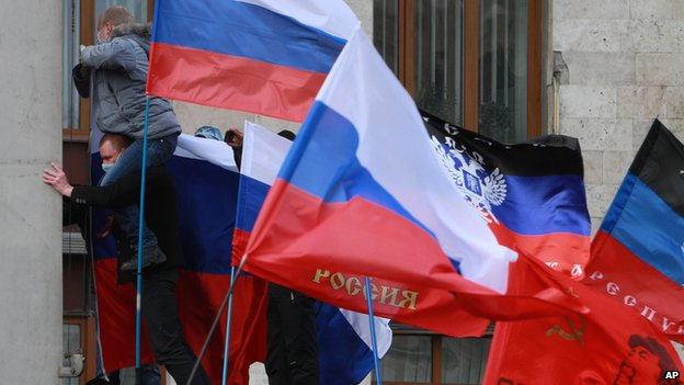Pro-Russian activists hoist Russian flags over an administrative office in Donetsk, Ukraine, on 1 March 2014