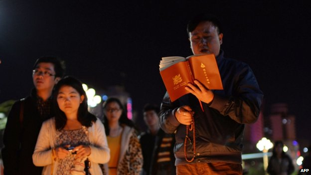 This picture taken on 2 March 2014 shows a Buddhist (R) chanting prayers as mourners light candles at the scene of the terror attack at the main train station in Kunming, southwest China's Yunnan province