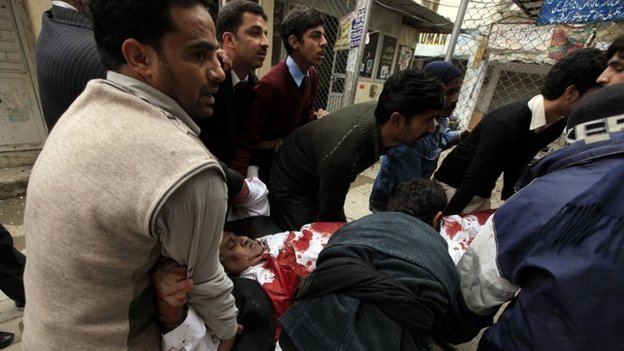 People carry an injured man from the site of a bomb attack at the district court in Islamabad March 3, 2014.