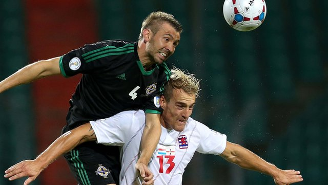 Gareth McAuley wins this aerial duel against Luxembourg