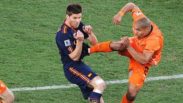Nigel de Jong puts in a high tackle on Xabi Alonso