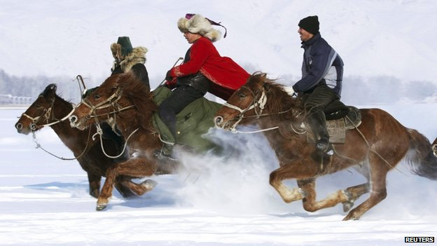 Herdsmen take part in a horse race during a local snow festival in Altay, Xinjiang region, 12 February 2014