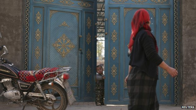 File photo of a child looking out from a door as a Uighur woman walks by in a residential area in Turpan, Xinjiang