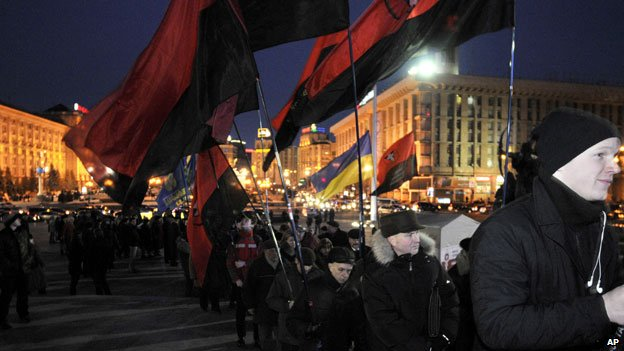 Protesters wave Ukrainian Insurgent Army flag
