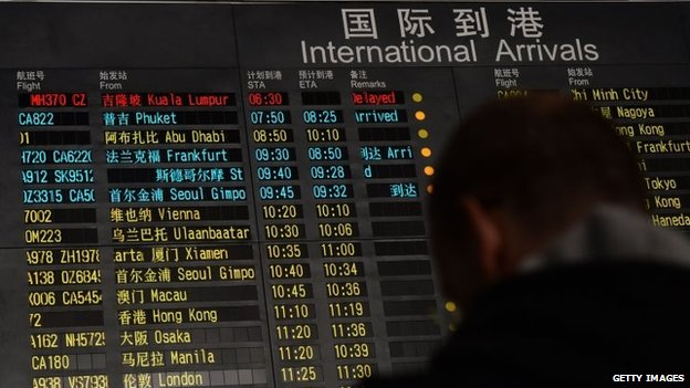 A man stands beside the arrival board at Beijing airport, which shows the missing flight MH370