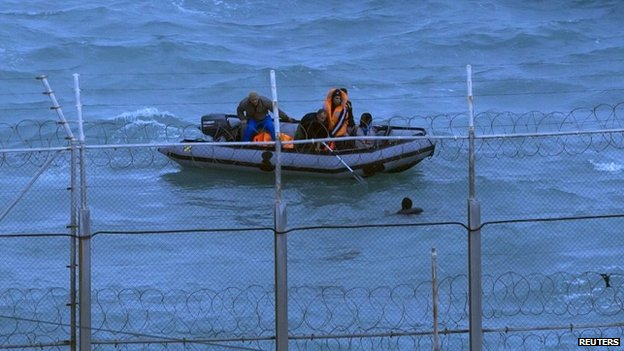 Moroccan soldiers remove a migrant from the water near Ceuta's border fence in 2014