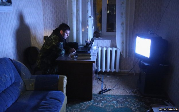 A Ukrainian soldier watches a news broadcast at the Belbek military base in Crimea (4 March)