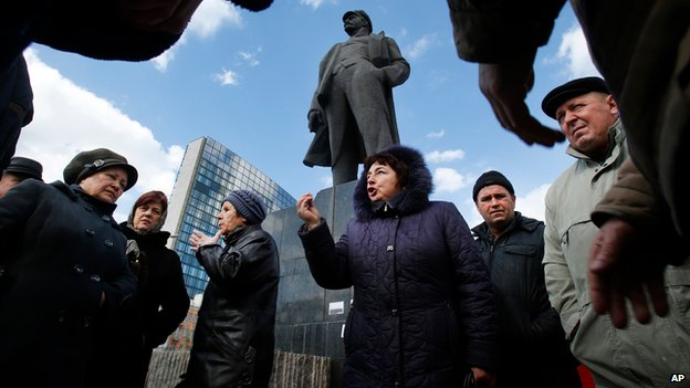 People discuss developments in front of Lenin statue in Donetsk, Ukraine, on 12 March 2014