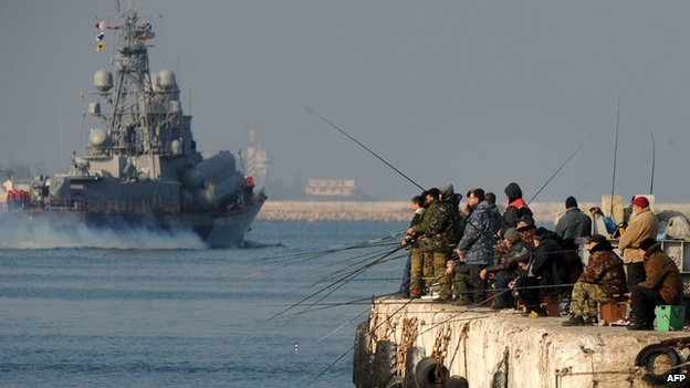 People fish as a Russian naval vessel passes by in Sevastopol bay, Crimea, on 12 March 2014