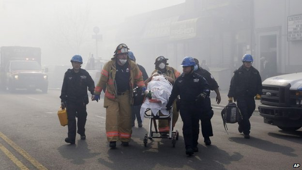 Rescue workers removed an injured person on a stretcher following a building explosion and collapse in East Harlem, New York City, on 12 March 2014