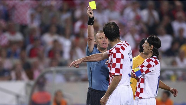 Graham Poll gives Croatia's Josip Simunic a yellow card
