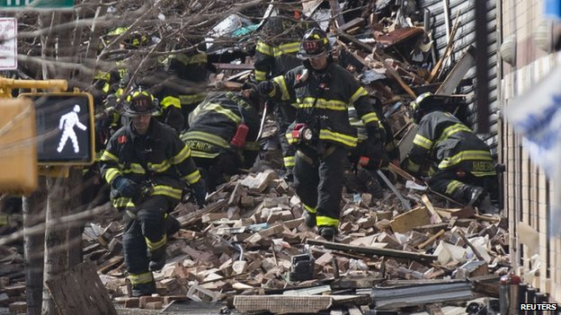 New York City fire fighters dig through rubble at a building explosion in New York City on 12 March 2014