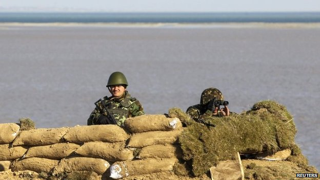 Ukrainian servicemen stand guard at a check point near a village in Kherson region, March 15