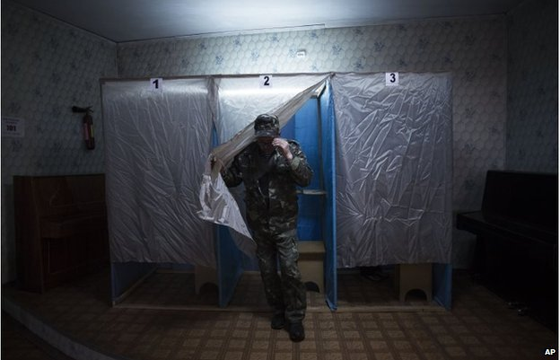 A member of a pro-Russia militia walks out of the voting cabin in Bachisaray, Ukraine, March 16