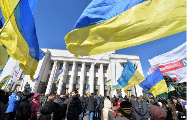 People hold Ukrainian flags as they gather in front of the parliament in Kiev on March 17