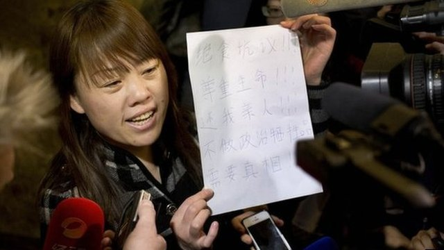 """A relative of a Chinese passenger aboard the missing Malaysia Airlines Flight MH370 shows a paper reading """"Hunger strike protest, Respect life, Return my relative, Don't become victim of politics, Tell the truth"""""""