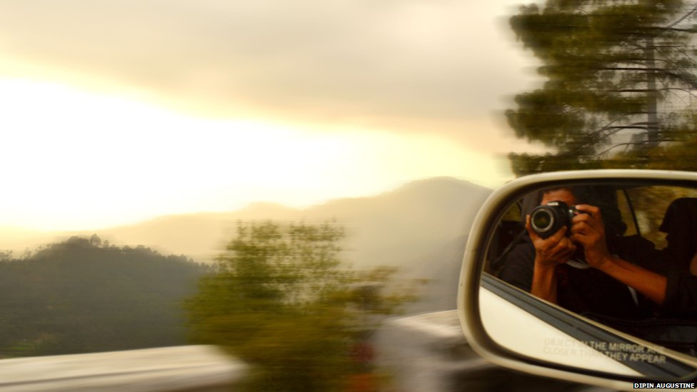 Photographer in car wing mirror