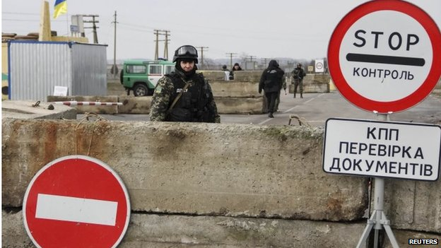 A Ukrainian soldier is seen at a checkpoint at the road near a Crimea region border 9 March 2014