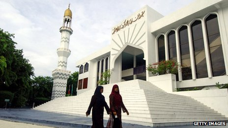 Two women walk past mosque