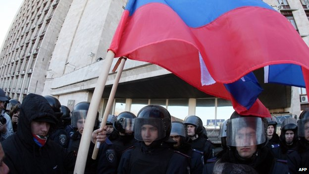 Pro-Russian activists in Donetsk, eastern Ukraine, hold Russian flags in front of riot police. Photo: