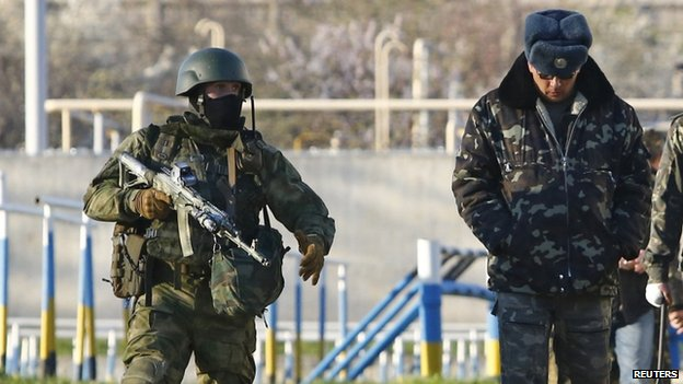 An armed Russian soldier (left) guards a Ukrainian officer at Belbek. Photo: 22 March 2014