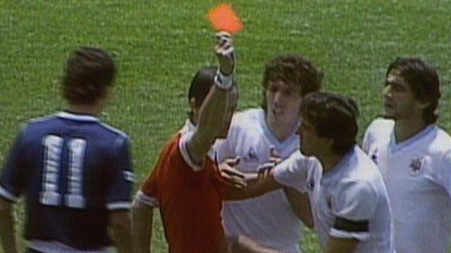 Referee Joel Quiniou sends off Uruguay's Jose Batista against Scotland