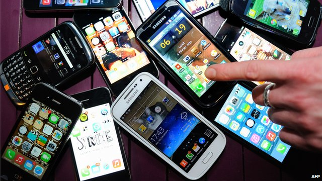 A finger points to a collection of smartphones