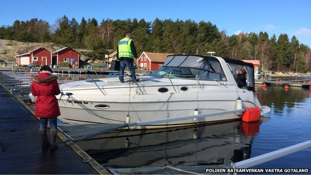 Police inspect an abandoned boat