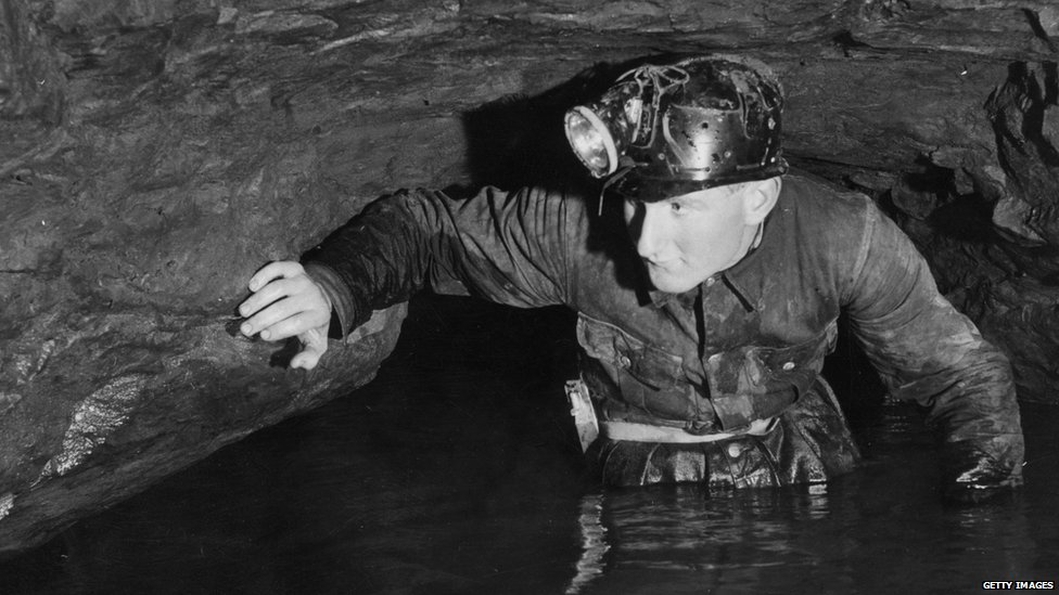 Caver John Buxton wades through limestone caves at Speedwell Water, Peak Cavern, in the Peak District, Derbyshire, circa 1960